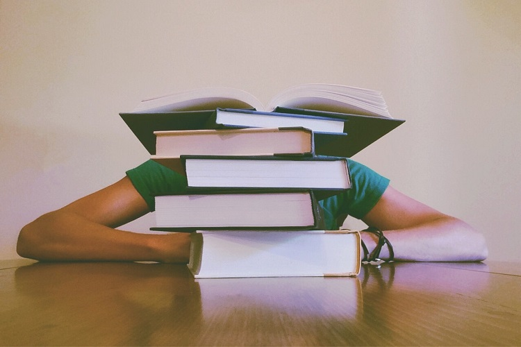 Student over a pile of books in H2 Chemistry tuition